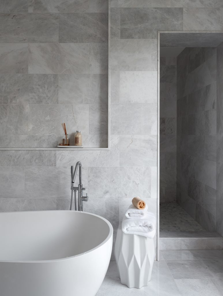 A portrait detail shot of the master ensuite. The focus of this image is on the tub, the stand up shower and the marble floors and walls.