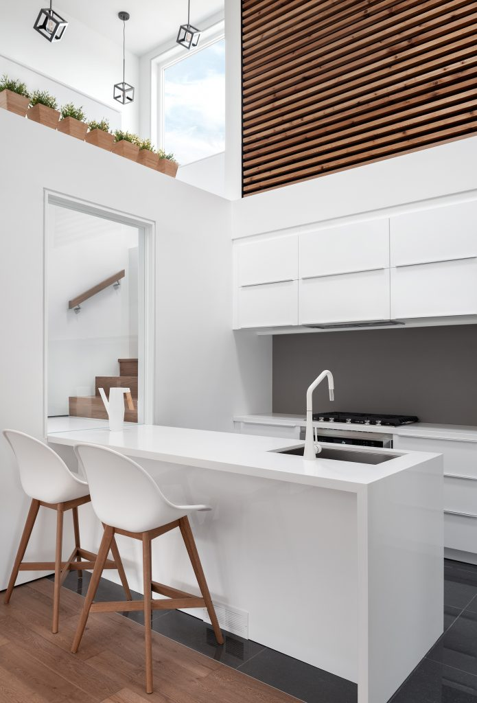 A portrait photograph of the kitchen. Stark whites and and ribbed wood panel walls add a very clean and modern touch to this interior.