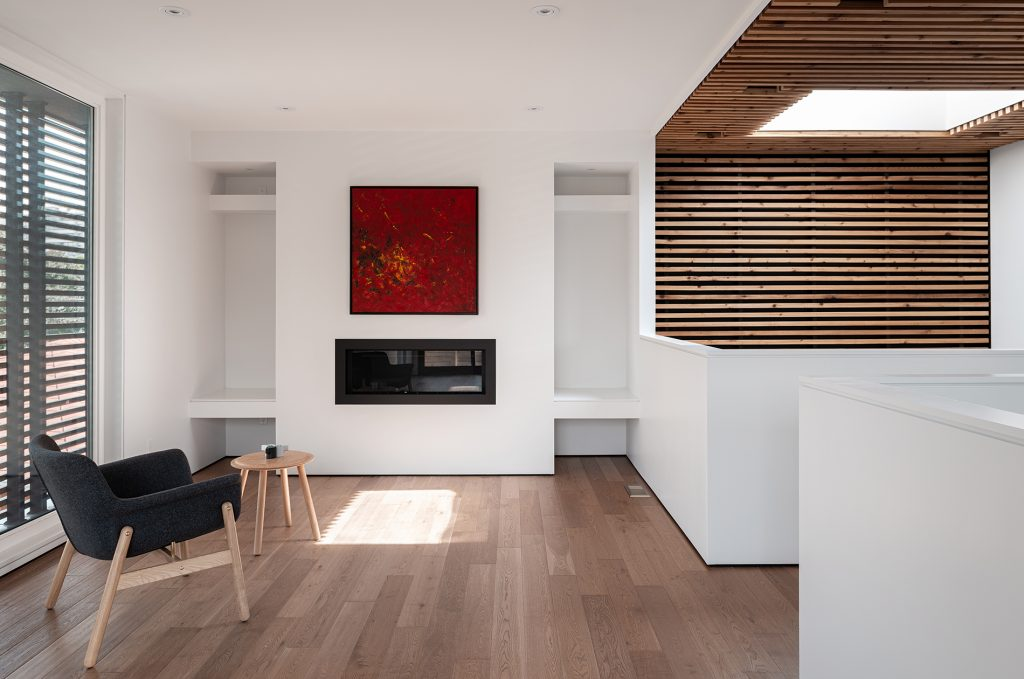 A one point perspective of the living space on the second floor. The interior design is very minimal with one chair and a small side table facing a fire place.