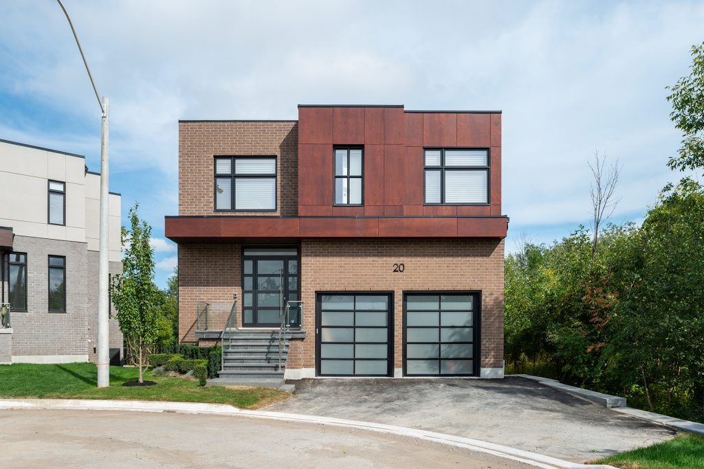 A photography of the exterior of the property. A cube shaped home backing onto Rouge Valley.
